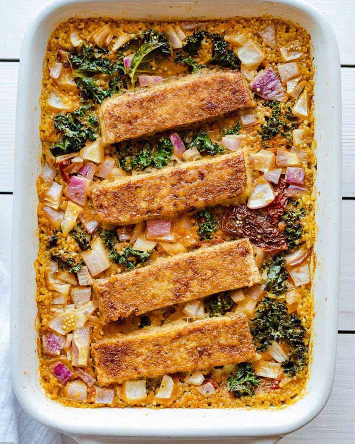Casserole dish with quinoa, red onion, kale, and sun-dried tomatoes cooked in vegetable broth and topped with soy-glazed tofu rectangles.
