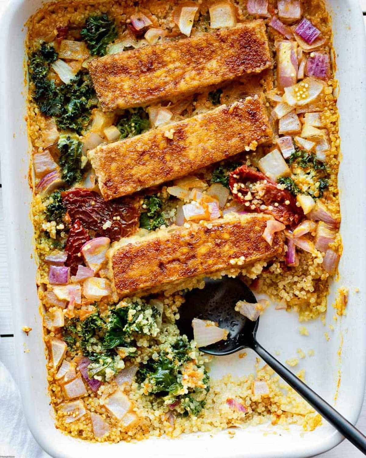 Tofu and quinoa casserole with sun-dried tomatoes, red onions and curly kale.