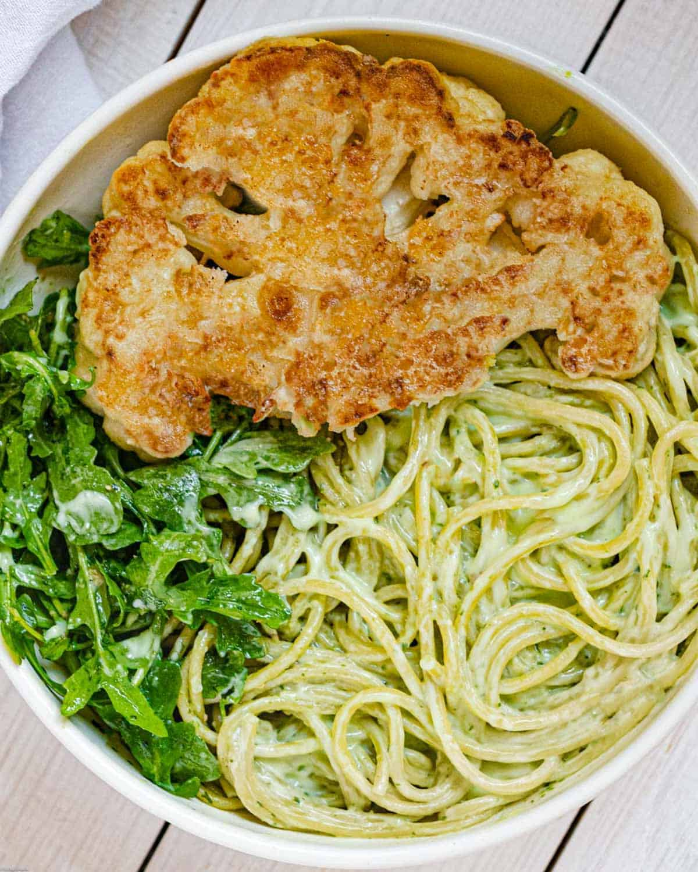 Spaghetti with light green avocado pesto, dressed arugula, and a crispy cauliflower steak.