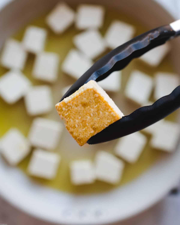 Crispy fried tofu cubes in a skillet.