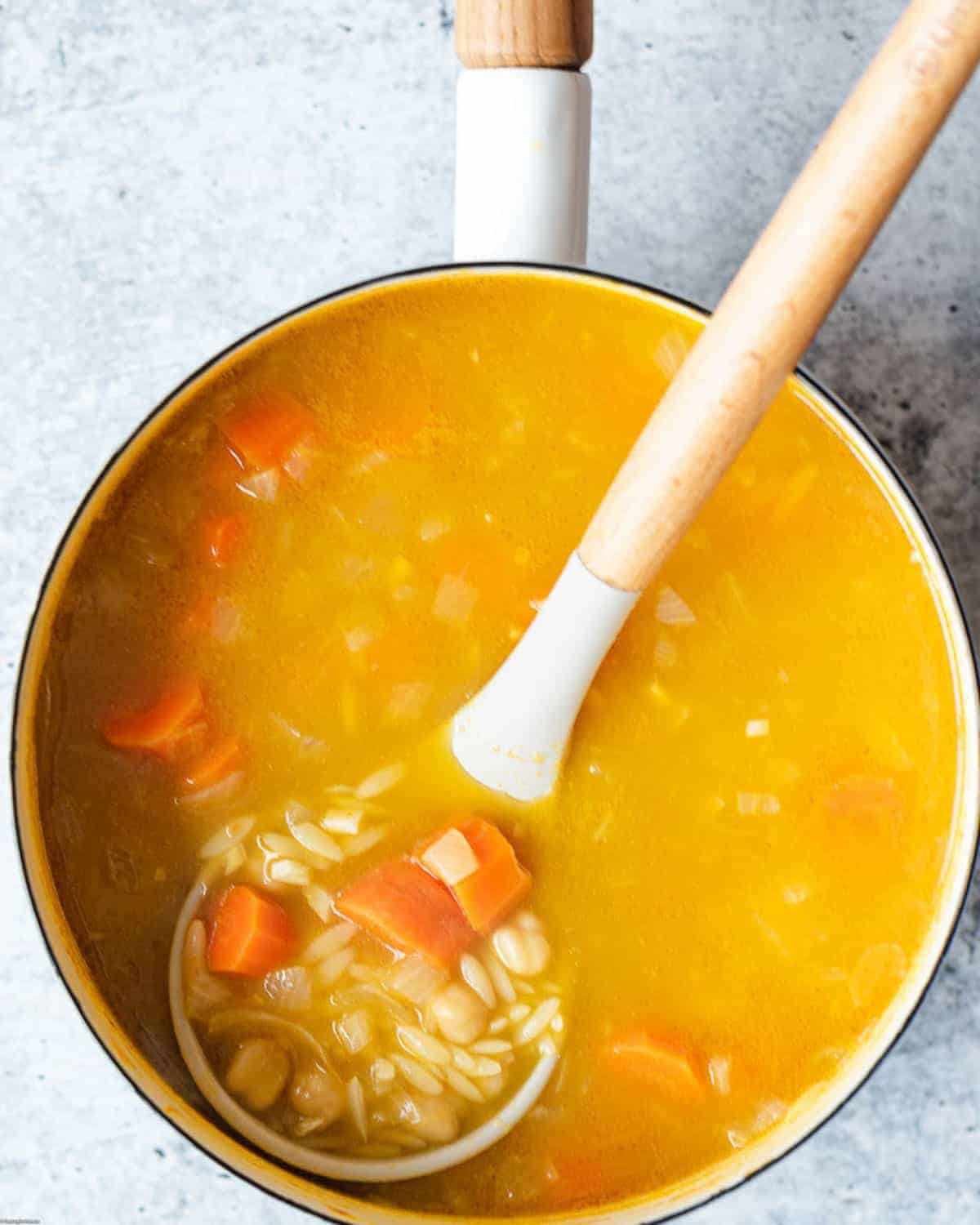 Saucepan chickpea miso soup with orzo, carrots, and onions in a golden vegetable broth.
