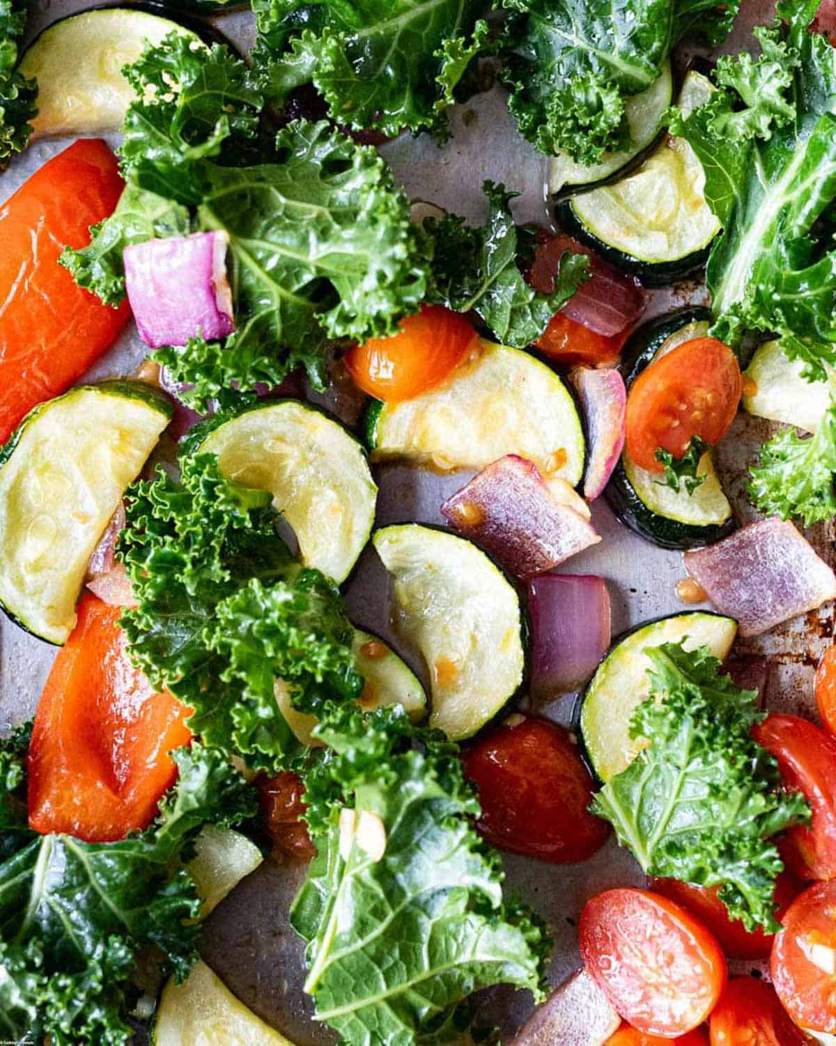 Roasted vegetables for the pasta salad. Chopped red onion, grape tomatoes, zucchini, and kale.