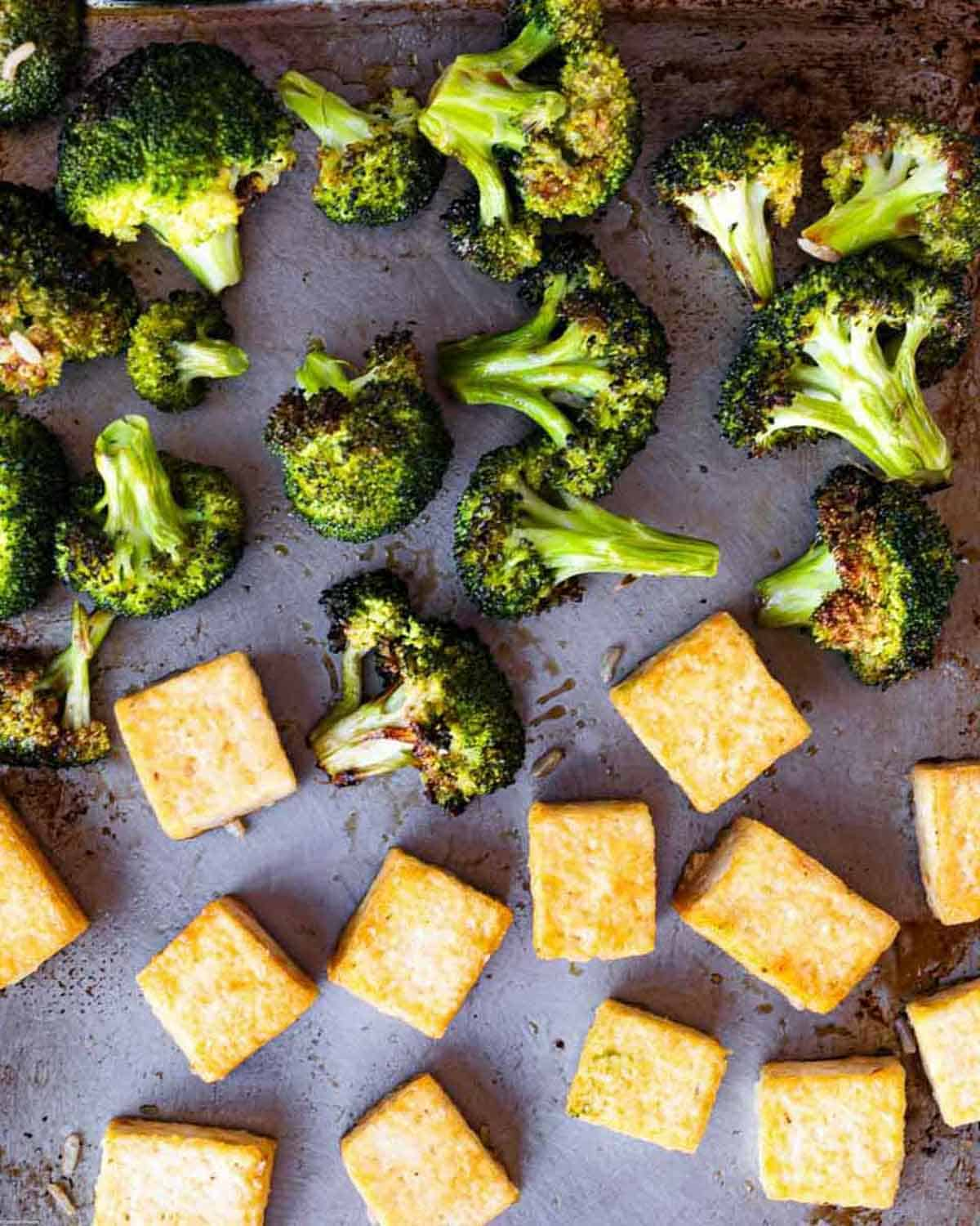 A large baking sheet with roasted charred broccoli and golden brown tofu cubes.