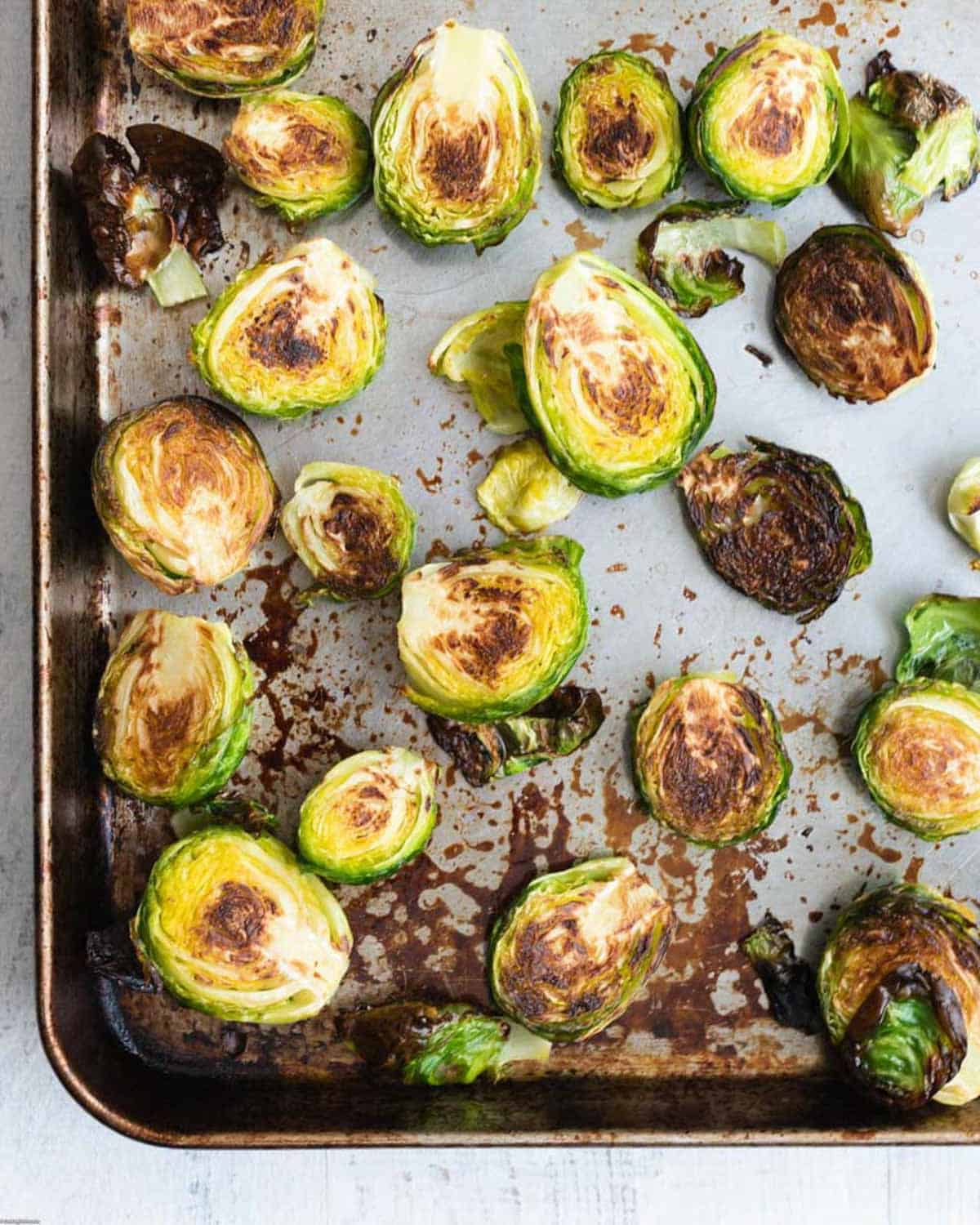 Roasted, charred Brussels sprouts on a large baking sheet.