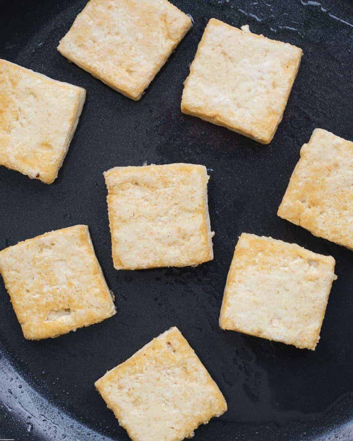 Pan fried, crispy tofu rectangles in a large skillet.