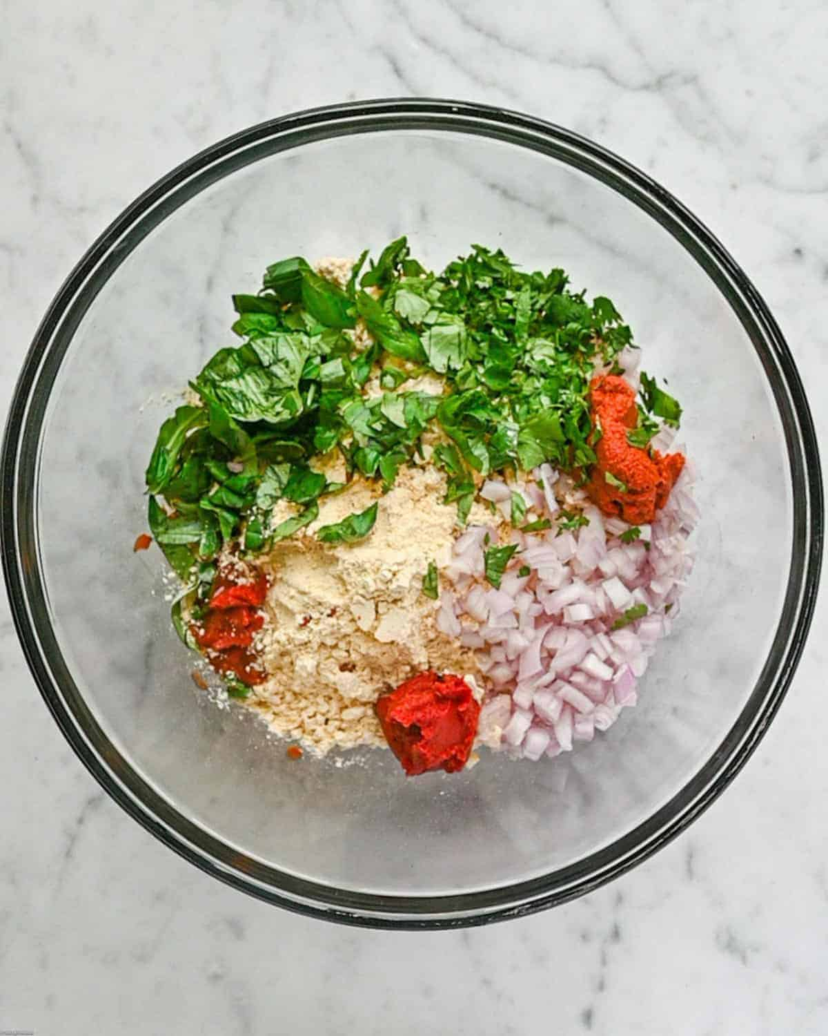 Thai red curry paste, sriracha, tomato paste, red onions, fresh basil, and cilantro in a bowl.