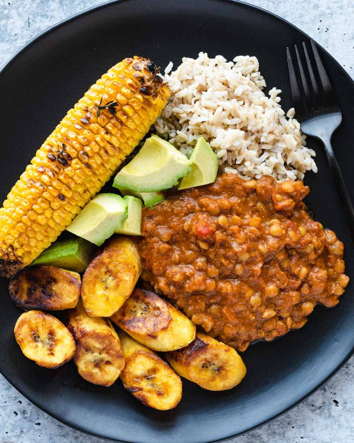 Lentil chili, roasted corn on the cob, diced avocado, crispy golden plantain, and brown rice.