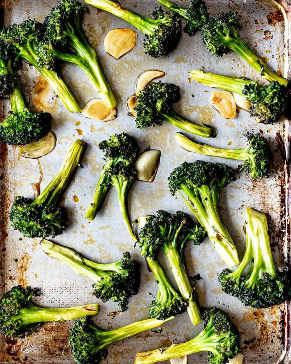 Roasted broccoli and garlic on a sheet pan drizzled with coconut aminos.