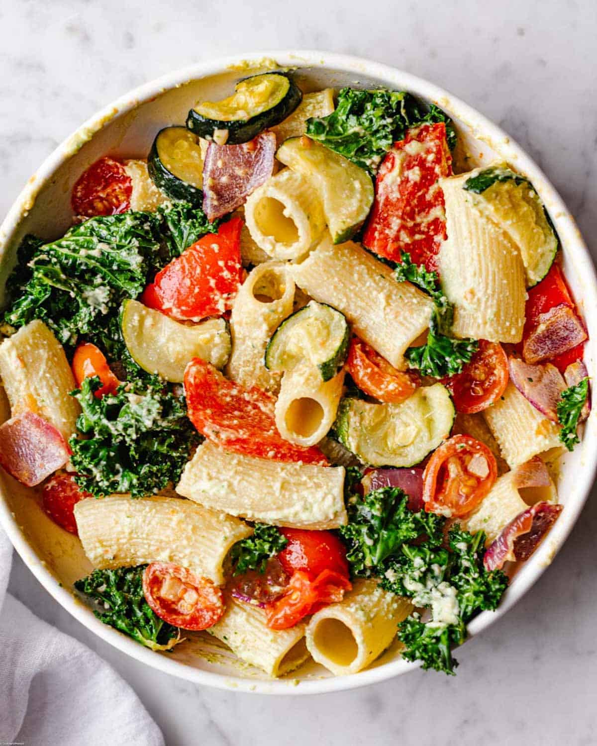Rigatoni pasta with roasted curly kale, grape tomatoes, and red onion in a creamy light green cilantro dressing.