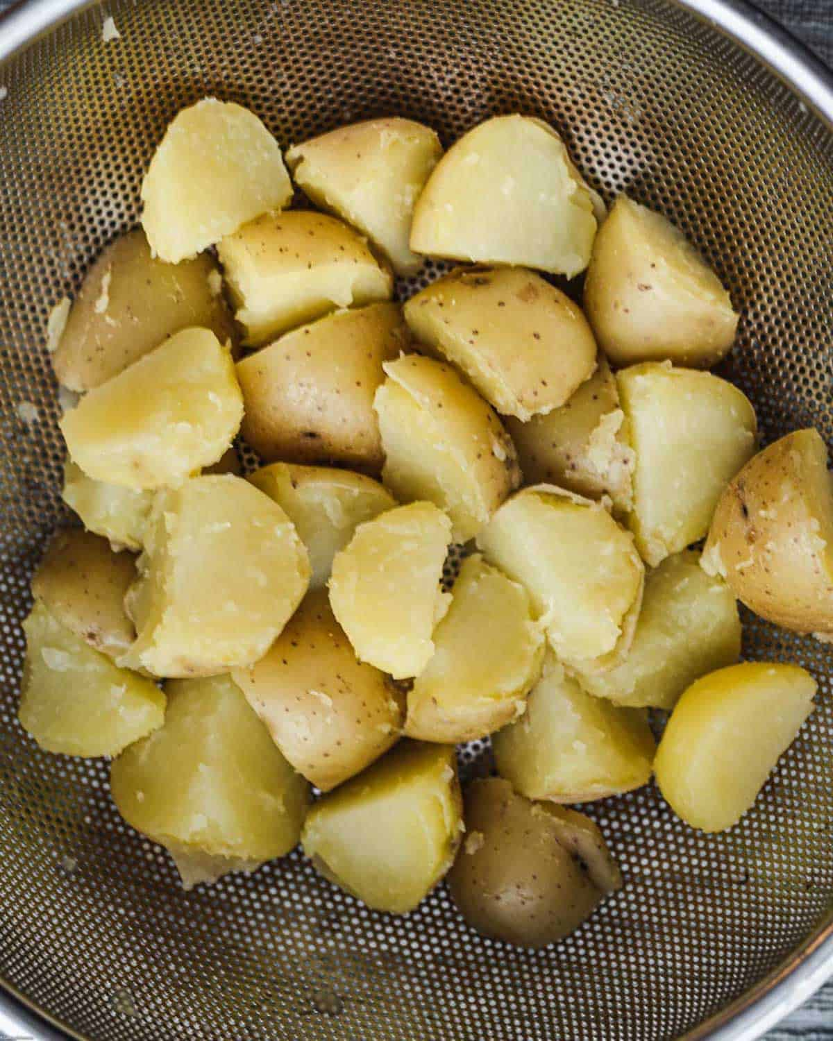 Simmered potato chunks in a colander, after being shaken to rough up the outer layer before roasting.