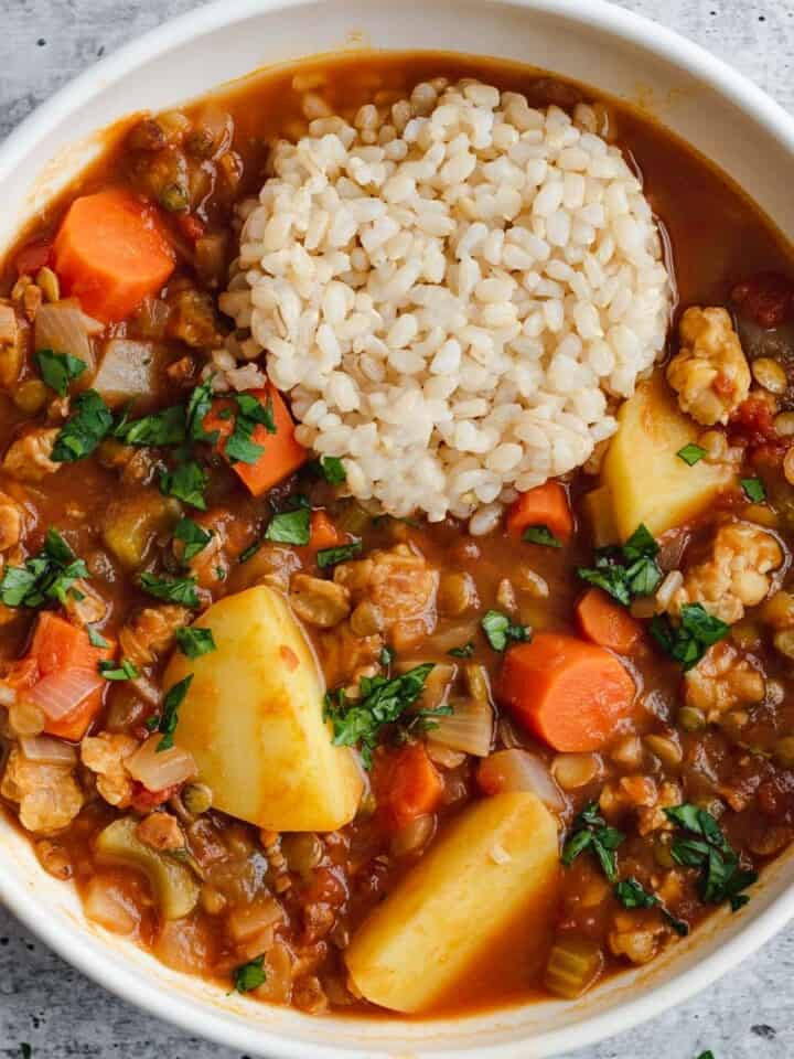 Tempeh, lentils, potatoes, and carrots in a tomato broth stew served with brown rice.