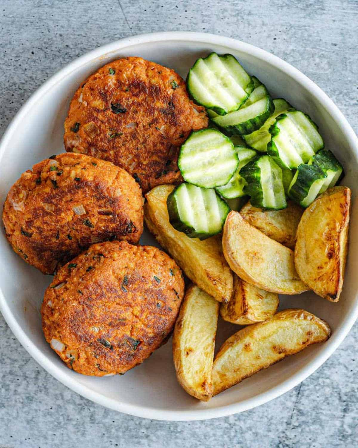 Tofu burgers with Thai seasoning, crinkle cut cucumbers, and home fries in a bowl.