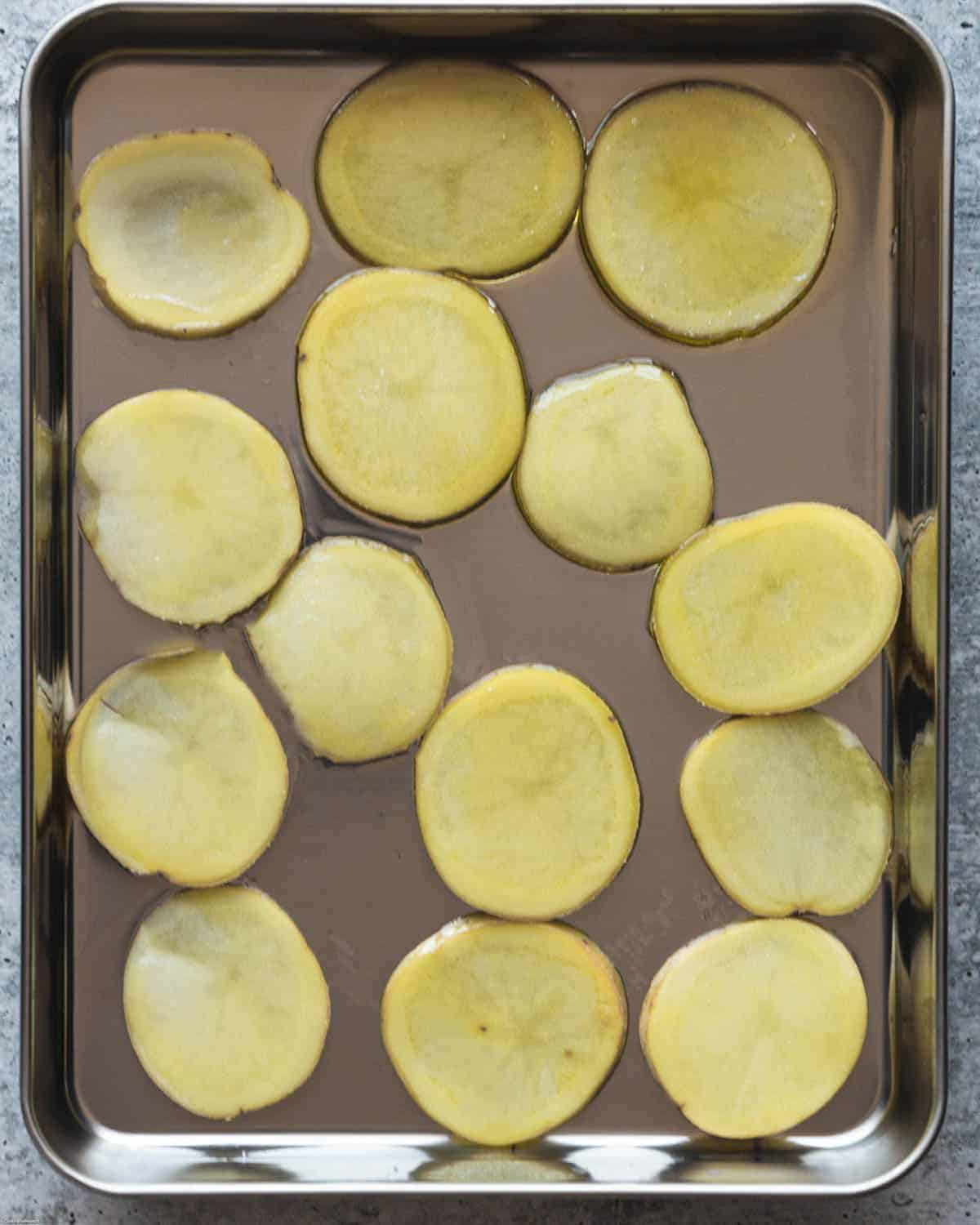 Thinly sliced potatoes on a baking sheet with a thin layer of oil. Ready to bake in the oven to make homemade baked potato chips.