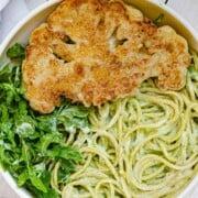 Crispy cauliflower steak with spaghetti and creamy vegan pesto sauce.