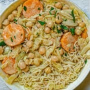 Chickpeas, carrots, green cabbage and ramen noodles in curry.