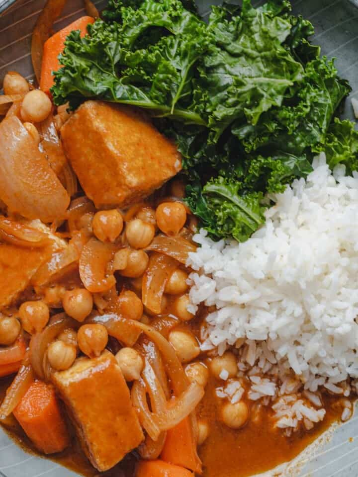Chipotle Chickpea & Tofu Stew served with white rice, and garlicky kale in a bowl.