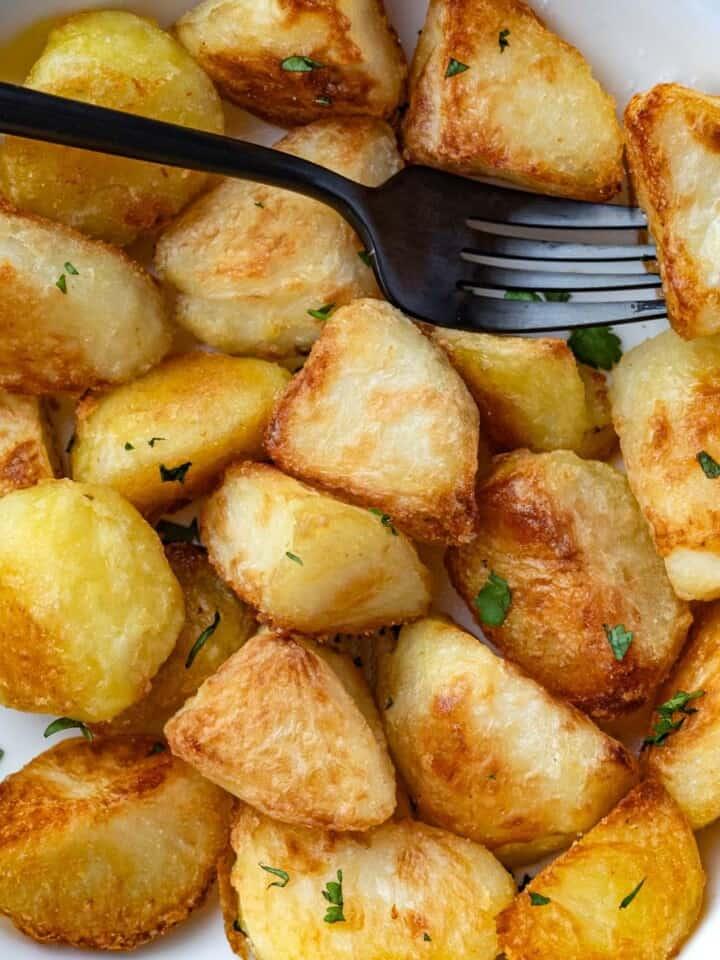 Golden brown crispy potato wedges with chopped cilantro garnish.