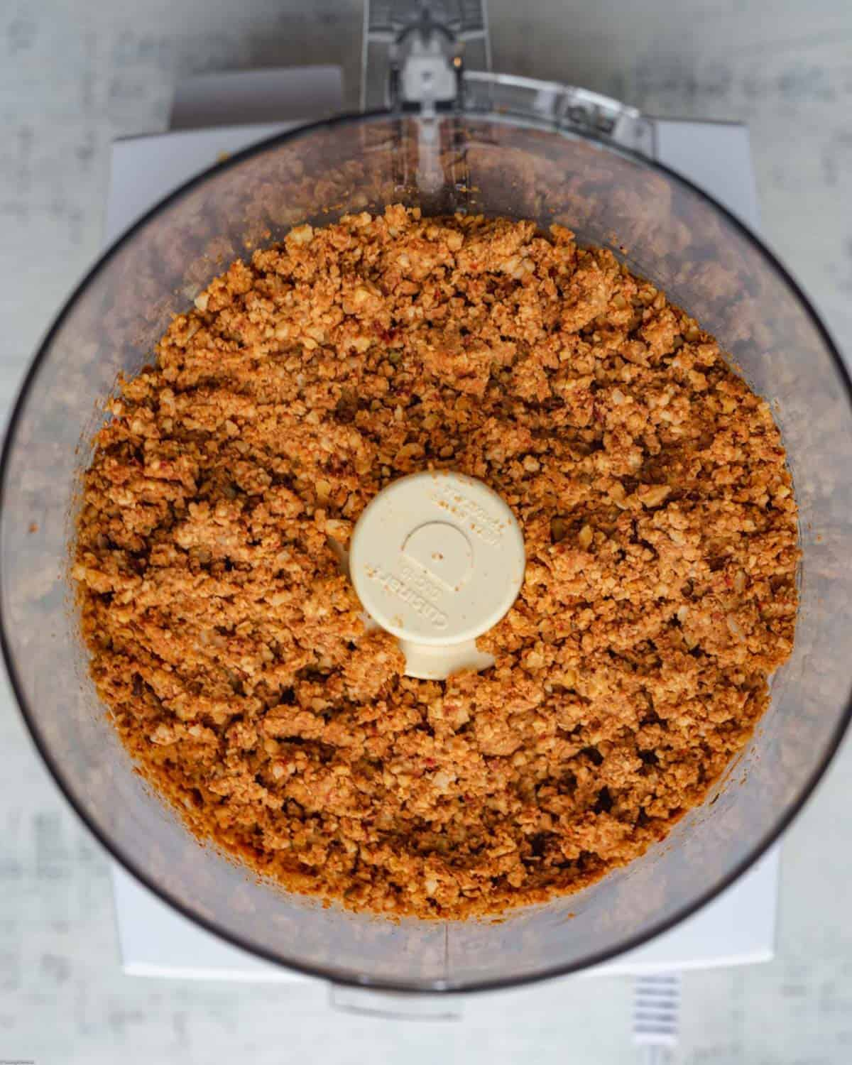 Crumbled tempeh with seasonings in a food processor for Sun-Dried Tomato Tempeh Burgers.