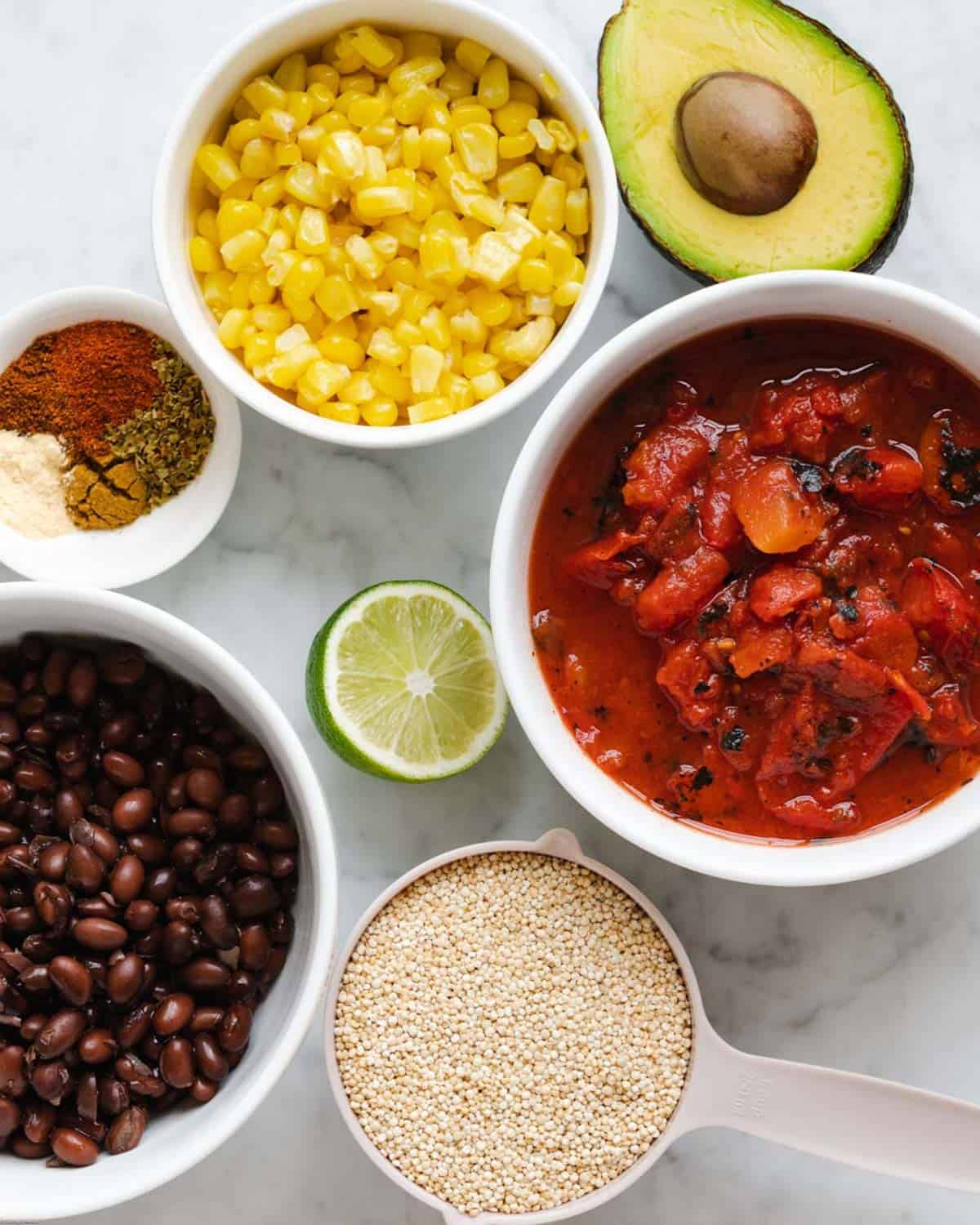 Ingredients for making Vegan Mexican Quinoa Bake: corn kernels, fire-roasted diced tomatoes, spices, black beans, quinoa, avocado and fresh lime juice.
