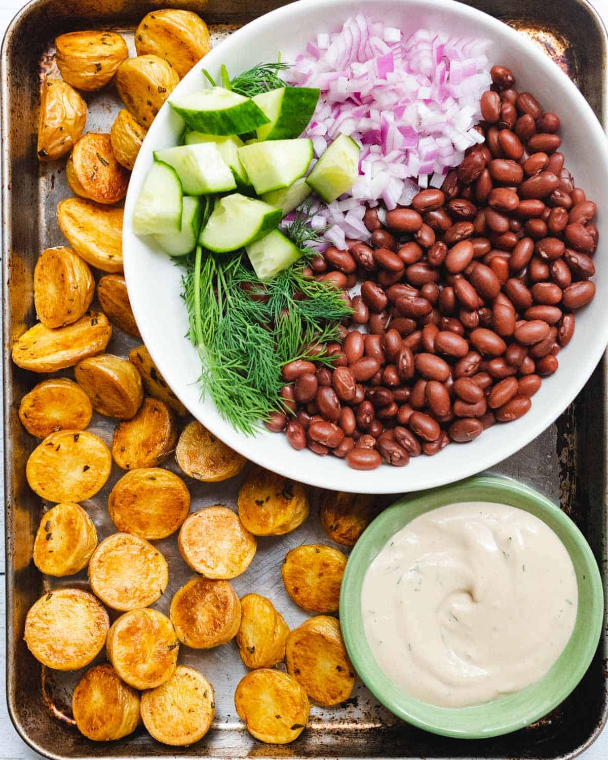 Roasted baby yellow potatoes, creamy Dijon tahini Dill dressing, chopped cucumbers and red onions, and fresh dill.