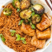 Saucy noodles with crispy tofu rectangles, and charred Brussels sprouts.