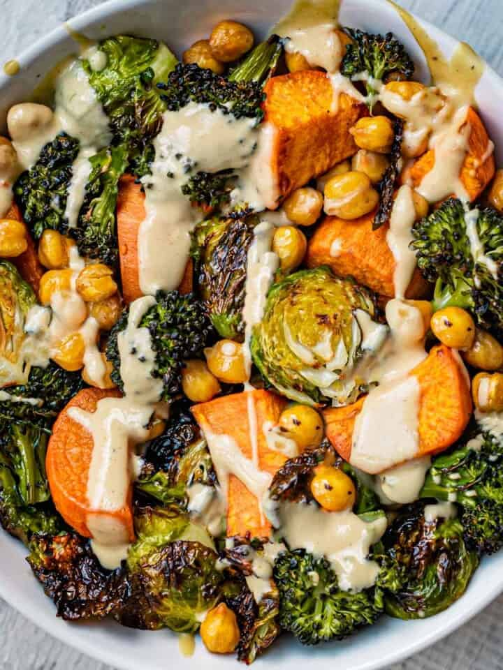 Roasted chickpeas, potatoes, and Brussels sprouts in a bowl with a drizzle of maple tahini dressing.