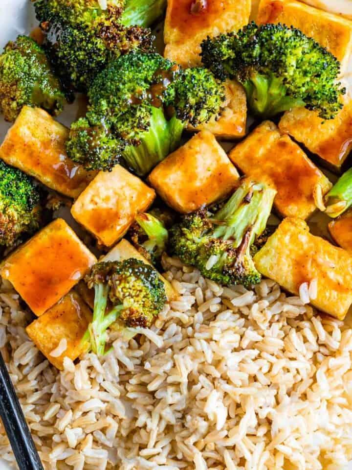 Crispy tofu cubes, broccoli florets, and brown rice in a brown teriyaki sauce.