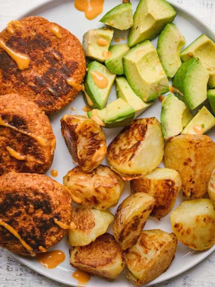 Sun-Dried Tomato Tempeh Burgers with crispy oven-baked potatoes and avocado chunks.