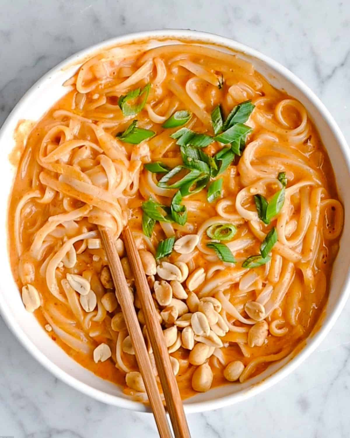 Thai Red Curry Noodles with chopped peanuts and scallions.