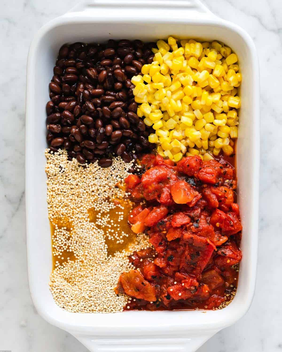 Diced tomatoes, corn kernels, black beans, spices, grain, and vegetable broth in a casserole dish.