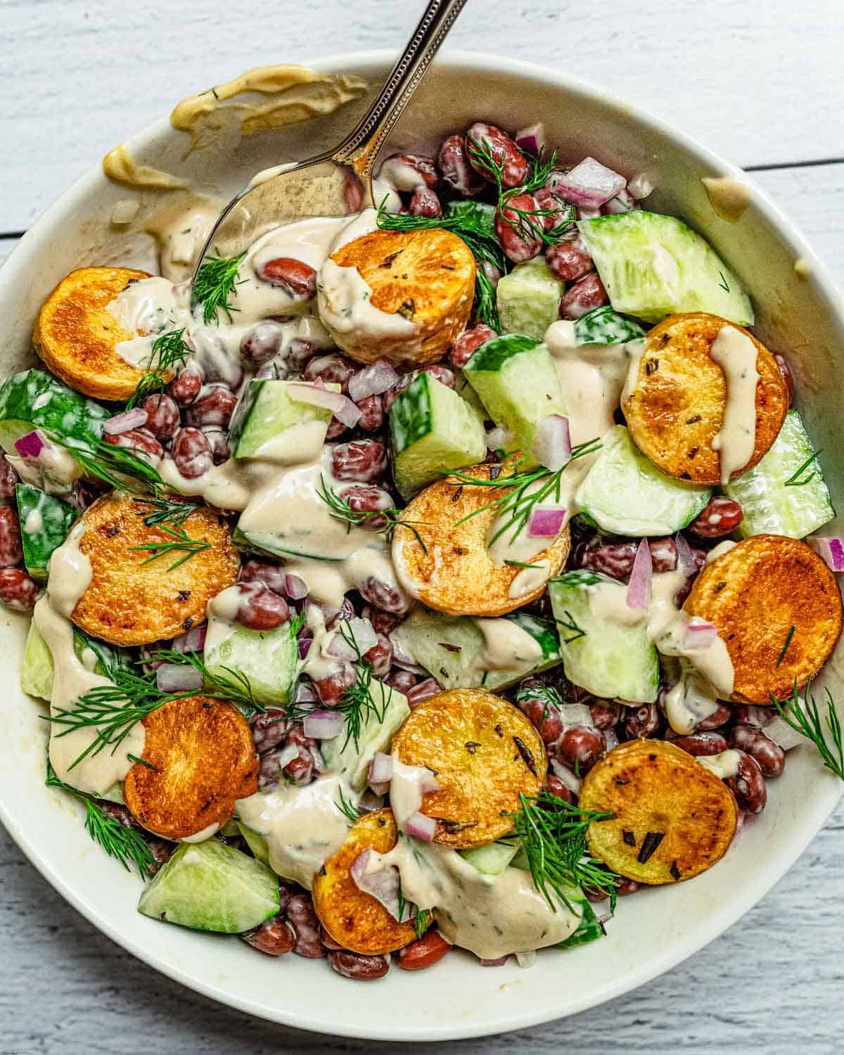Roasted baby potatoes, chopped cucumbers, and red beans in a creamy dill dressing.