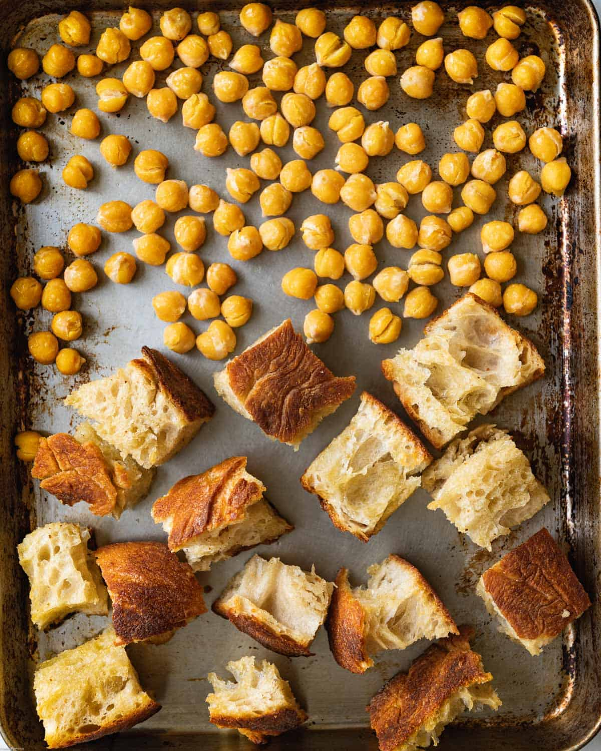 Baked ciabatta bread and chickpeas on a large baking sheet.