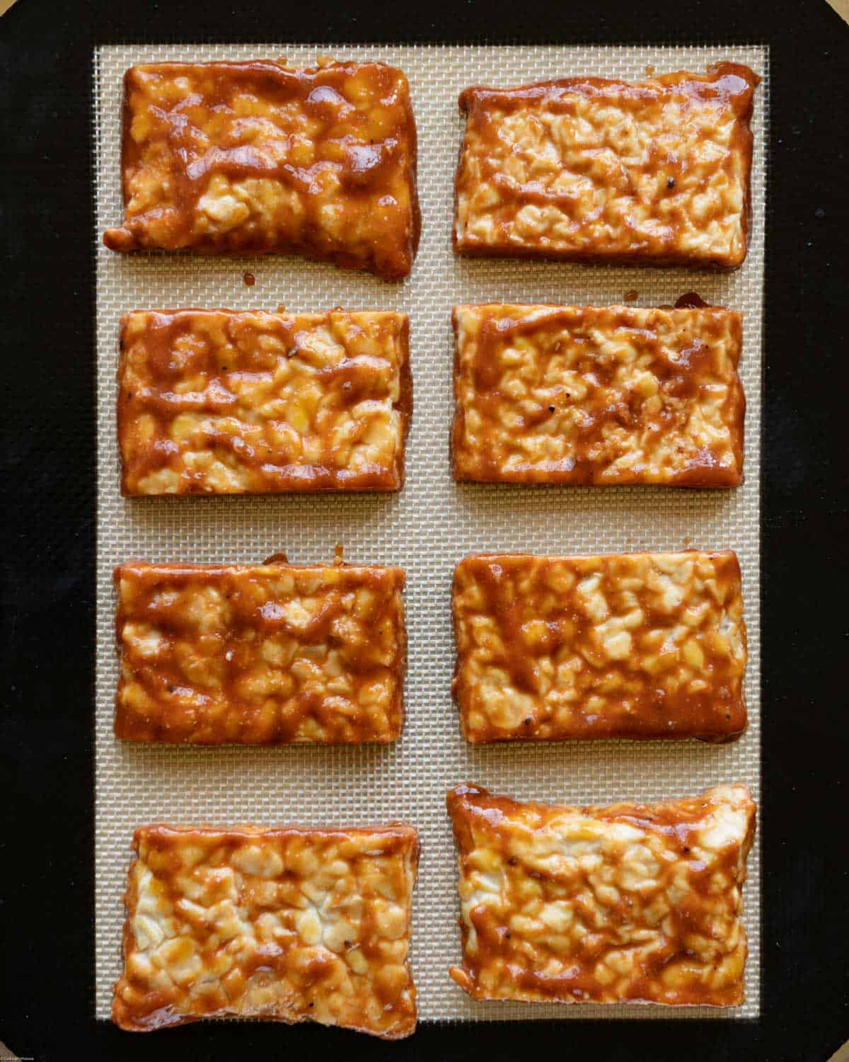 Marinated tempeh rectangles on a silicone baking mat.