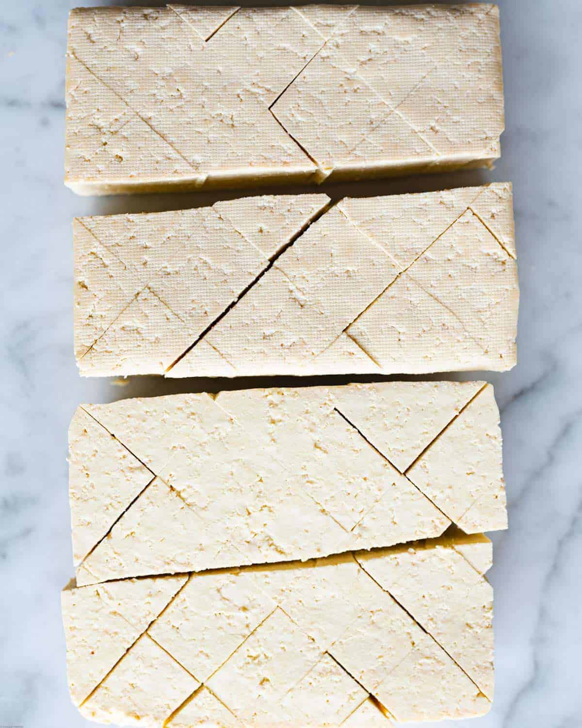 Extra firm tofu cut into 4 rectangles with a crosshatch pattern.