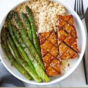Baked tofu steaks with sautéed asparagus and brown rice.