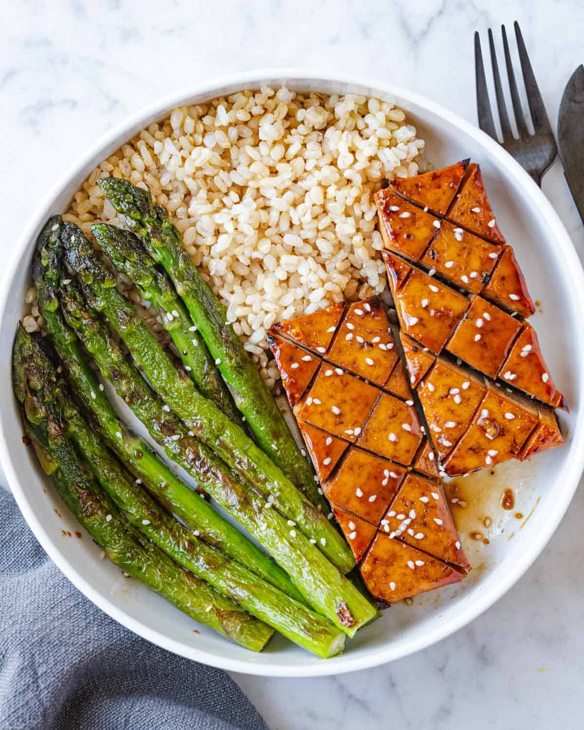 Browned asparagus spears with soy glazed baked tofu and brown rice.