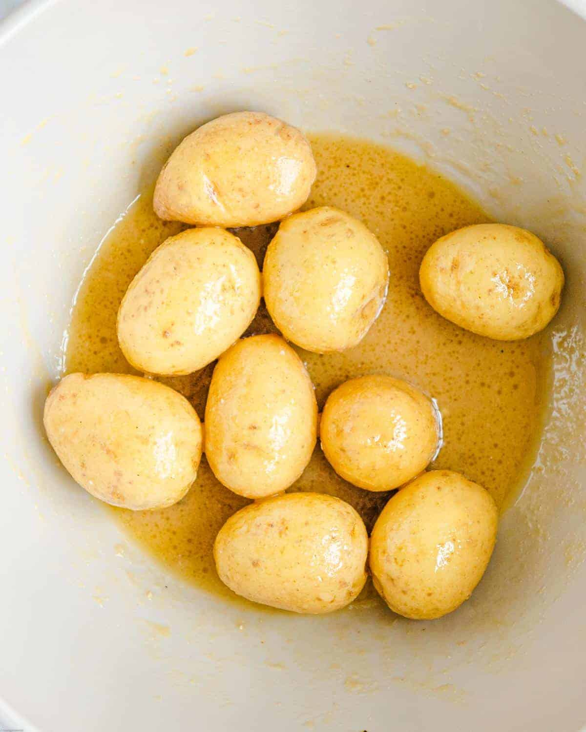 Whole baby yellow potatoes in a bowl with dressing.