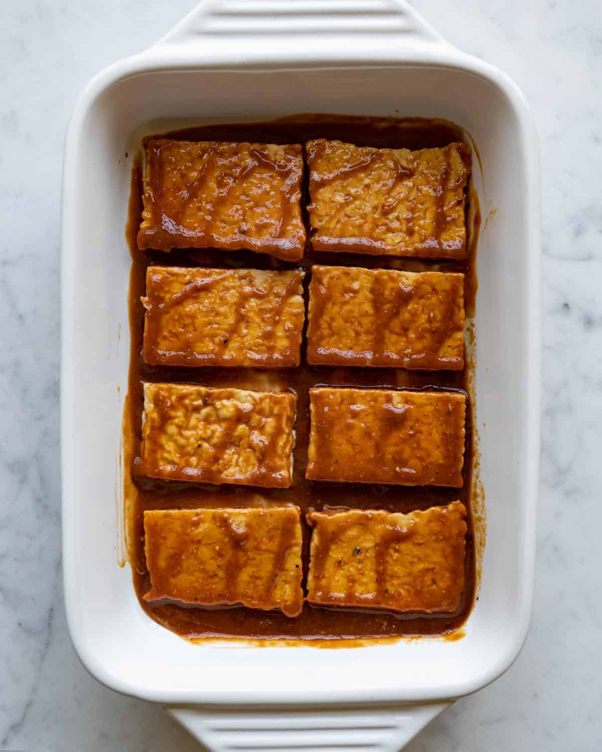 Tempeh rectangles in the umami marinade in a white casserole dish.