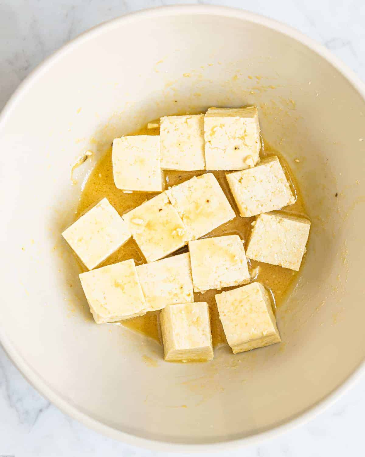 Tofu cubes in a bowl with the dressing.