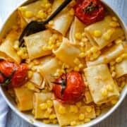 Paccheri pasta, tomatoes, sweet corn and miso butter in a white bowl.