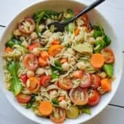 White bowl with chopped carrots, halved cherry tomatoes, salad leaves, chickpeas, avocado, and orzo pasta.