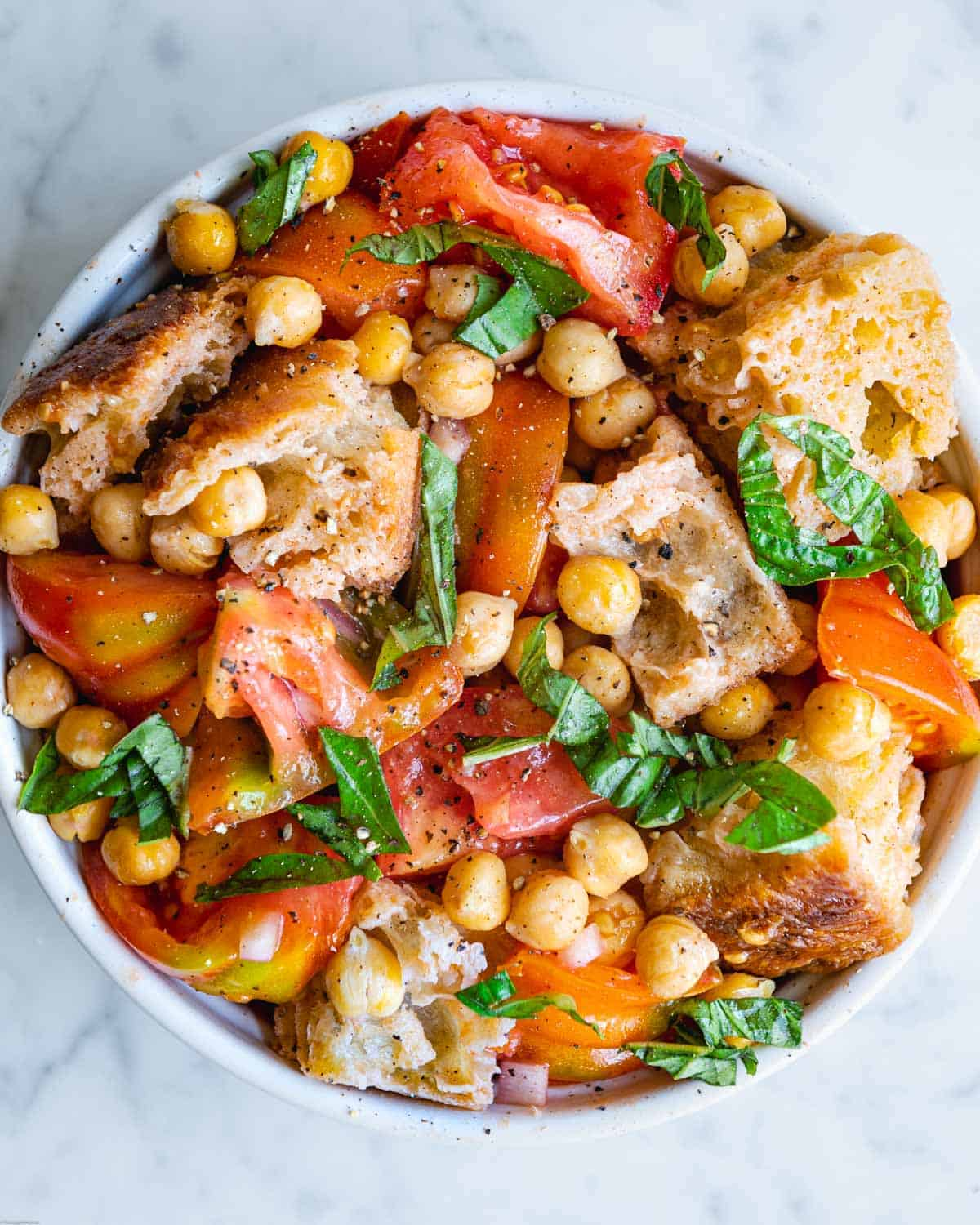 Panzanella salad with roasted chickpeas, bread, tomatoes, fresh basil and olive oil dressing.
