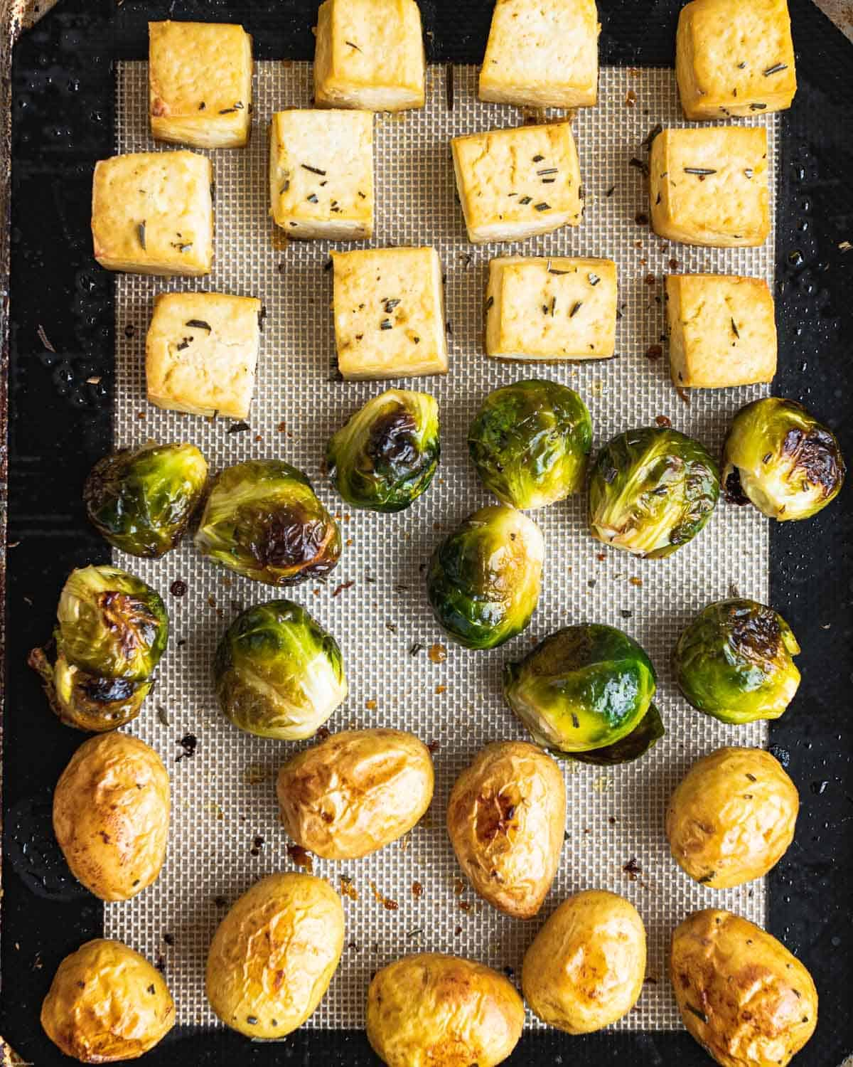 Baked Baby potatoes, Brussels sprouts, and cubed tofu on a baking sheet.