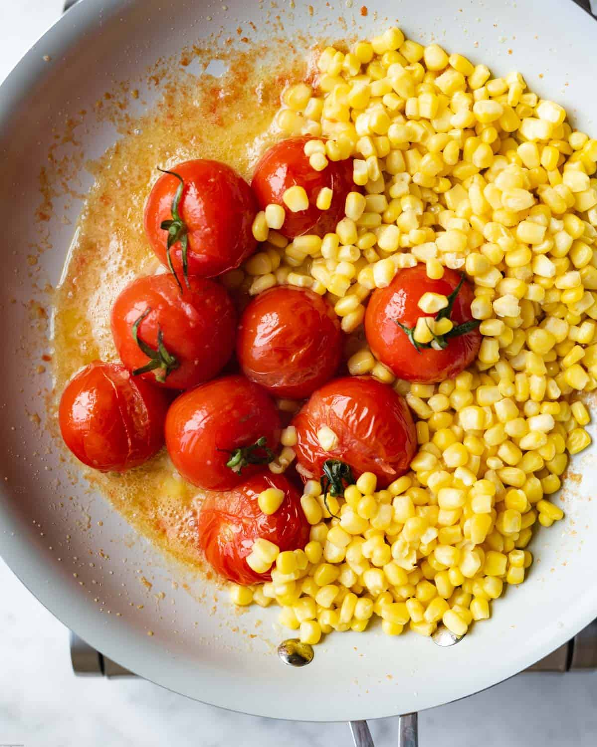 Sweet corn kernels and burst tomatoes cooking in a large skillet.
