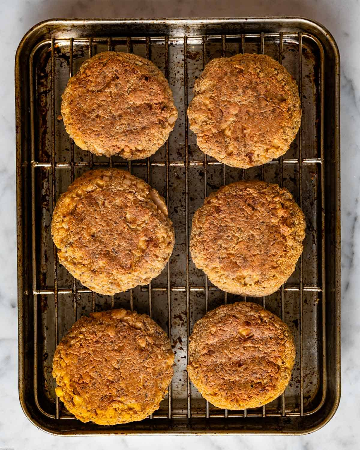Baked vegan chipotle tofu burgers on a cooling rack.