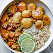 Bean curry with roasted potatoes, brown rice, lime, and cilantro in a bowl.