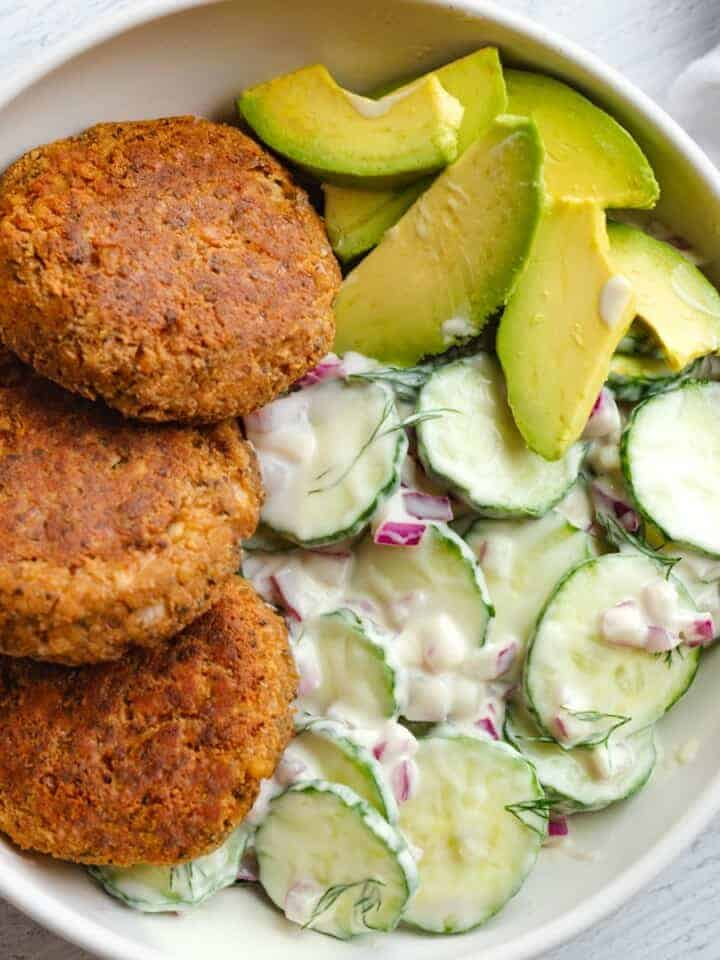 Easy Vegan Chipotle Tofu Burgers, creamy cucumber salad, and sliced avocado in a bowl for serving.