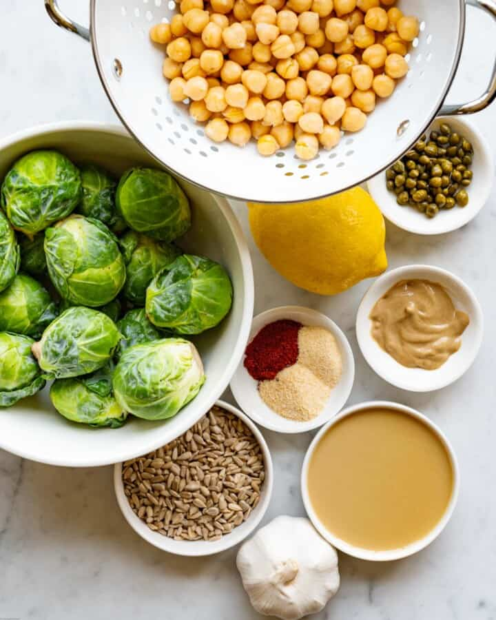 Chickpeas,Brussels sprouts, lemon, tahini, mustard, garlic, capers with brine, sesame seeds, and spices for making Chickpea & Brussels Vegan Caesar Salad.