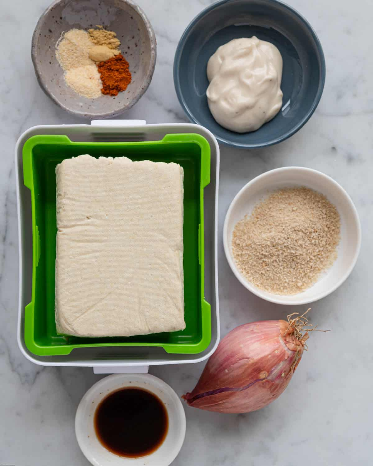 Extra-firm tofu in a press, Worcestershire sauce, shallot, breadcrumbs, mayonnaise, and spices.