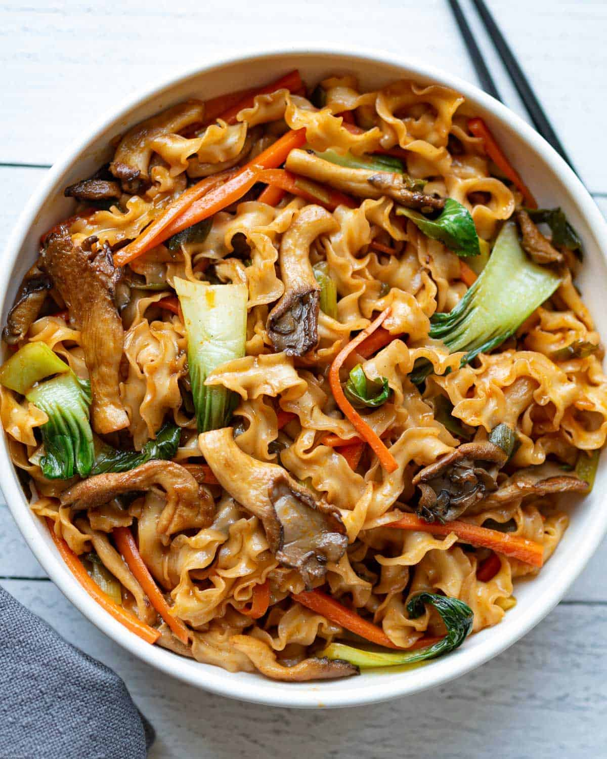 Guanmiao noodles, mushrooms, baby bok choy, carrots, green onions, and an Asian-inspired sauce. Mixed in a bowl for serving.